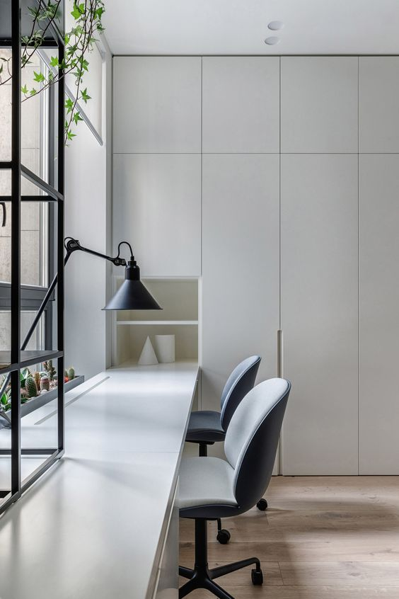 a clean minimalist home office with light grey storage units and a built-in shared desk, grey chairs and a table lamp is welcoming
