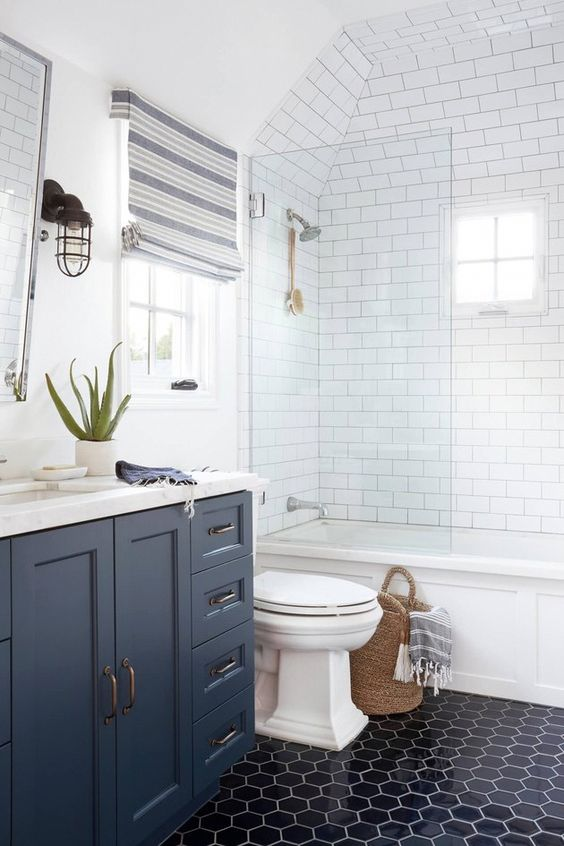 a coastal bathroom with navy hexagon tiles and a navy vanity, striped Roman shades, baksets with striped textiles is cool