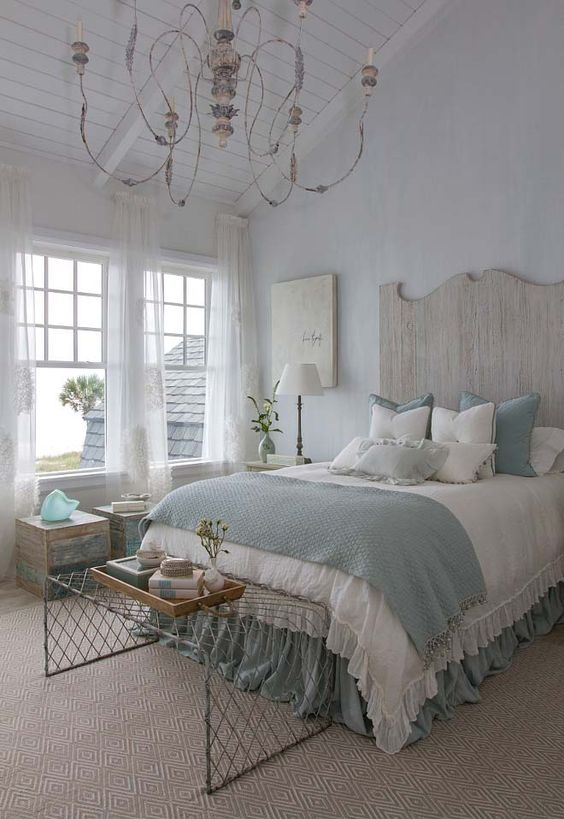 a coastal shabby chic bedroom with a wooden bed with a statement headboard, blue and white bedding, wooden furniture, a crystal chandelier and a wire bench