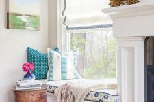 a cool and chic window nook with a Roman shade, a windowsill daybed with printed bedding and a small side table and blooms