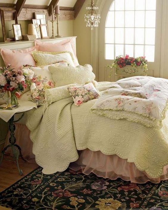 a cozy French country and shabby chic bedorom with a crystal pendant lamp, chic furniture, pastel bedding and lots of blooms