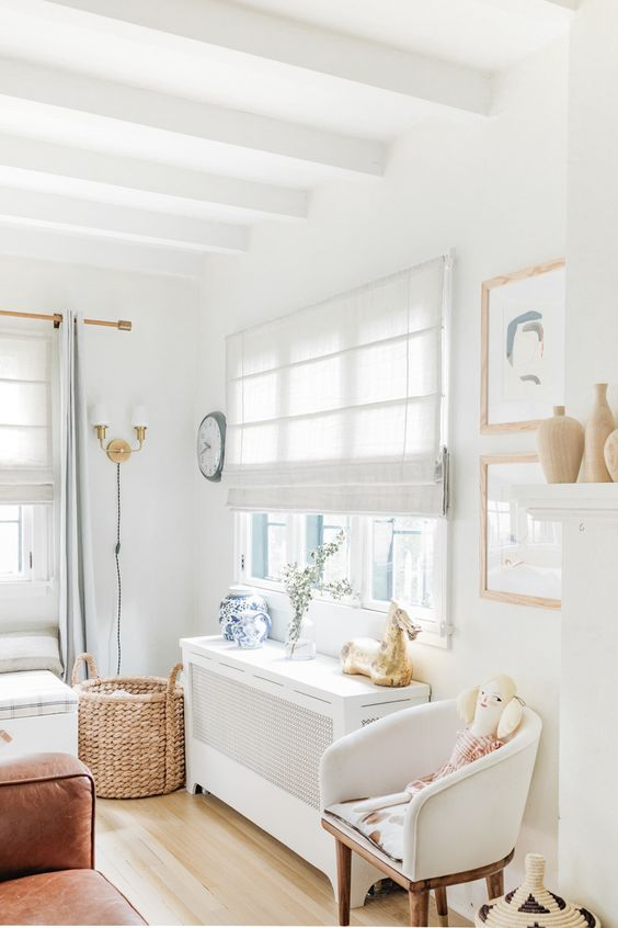 a cozy and serene kid's bedroom with a neutral Roman shade and neutral furniture looks welcoming and very airy