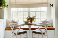 a cozy farmhouse dining space with a creamy Roman shade, a windowsill seat, a round table and woven chairs is lovely