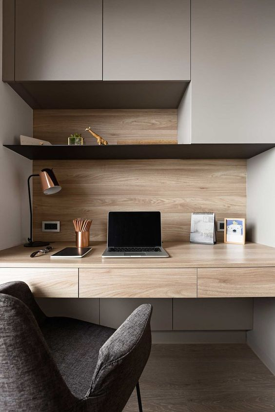 a cozy minimalist home office with sleek storage units, an open shelf and a built-in desk, a comfy chair and a copper table lamp
