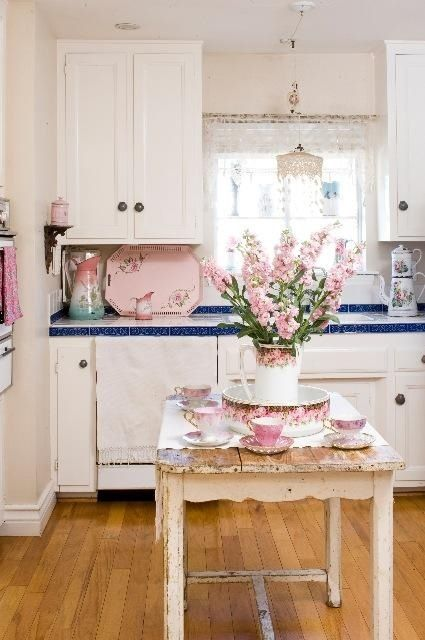 a cute shabby chic kitchen with white cabinets, blue tile countertops, a shabby table and touches of pastel pink