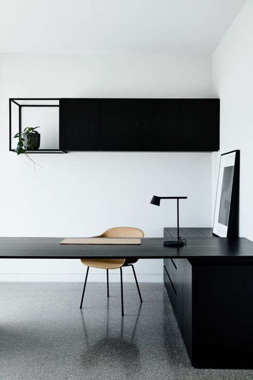 a dramatic minimalist home office with a large corner desk with storage, a black table lamp and a sleek storage unit with an open compartment