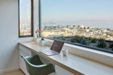 a dreamy minimalist home office wiht a large window for a view, a large desk with storage and a green chair is a fabulous space to work