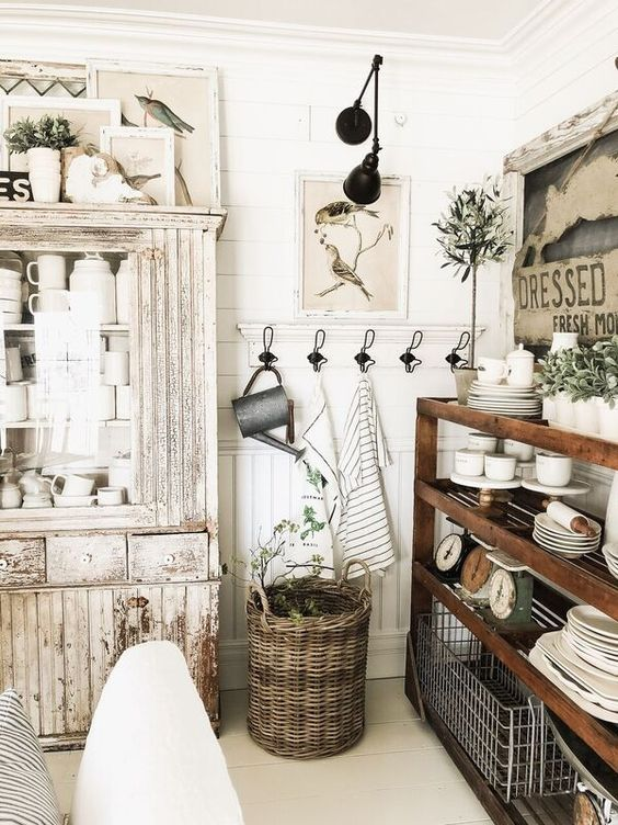 a farmhouse shabby chic kitchen with a stained open storage unit, white shabby furniture, greenery in pots and vintage artworks