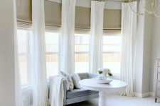a gorgeous bay window with burlap Roman shades and creamy curtains is a lovely idea for a refined neutral interior like this one