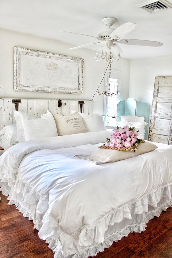 a gorgeous shabby chic bedroom in white, with a wooden bed and an artwork, a mint screen, a fan, neutral bedding with ruffles