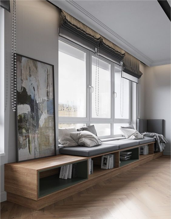 a large window with grey Roman shades and a large shelf with books that doubles as a daybed or a windowsill seat and styled with pillows