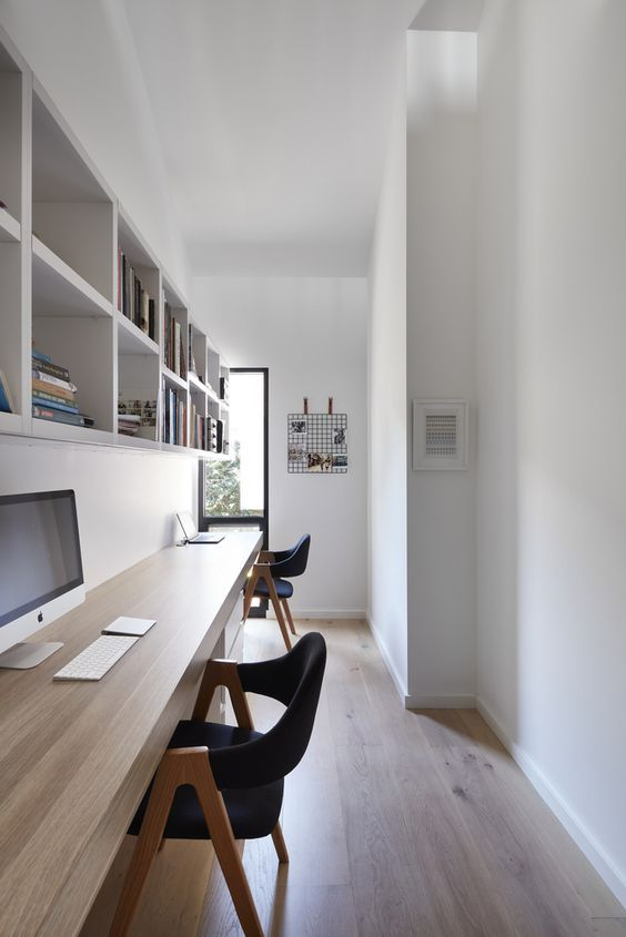 a long and narrow minimalist home office with shelving units and a floating double desk, comfy black chairs and much natural light