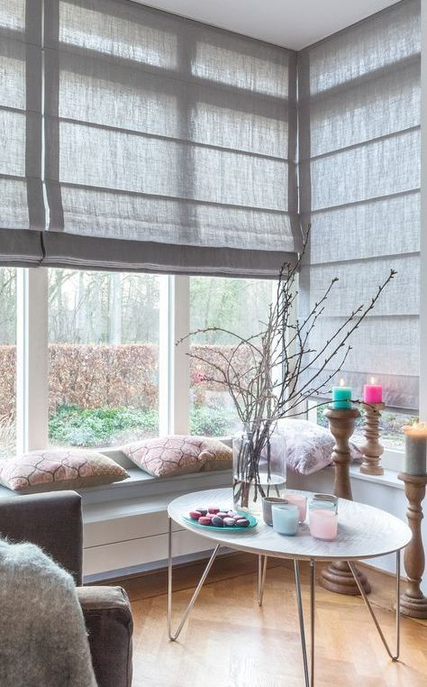 a lovely and cozy nook with a corner window, grey Roman shades, windowsill benches, a round table and bright touches