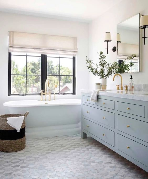 a lovely coastal bathroom with a hex floor, a light blue vanity, a mirror, gold touches and a neutral Roman shade to add interest to the space