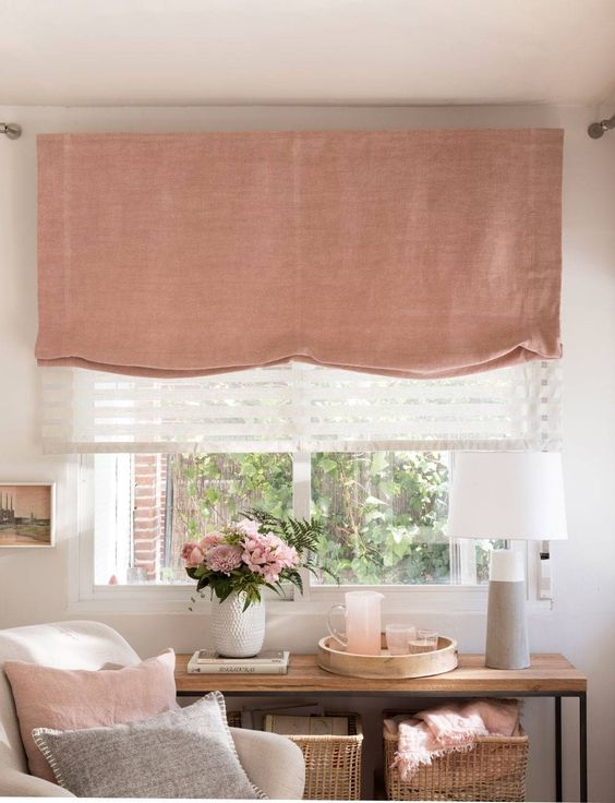 a lovely feminine space with a pink Roman shade that echoes with other pink decor in the room and makes it cooler