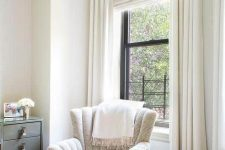 a lovely reading nook by the window styled with a printed Roman shade and creamy curtains is very lovely