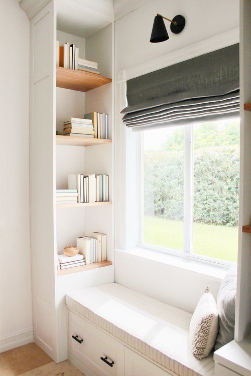 a lovely reading nook with built-in shelves, an upholstered windowsill daybed, a graphite grey Roman shade for blocking out the sun
