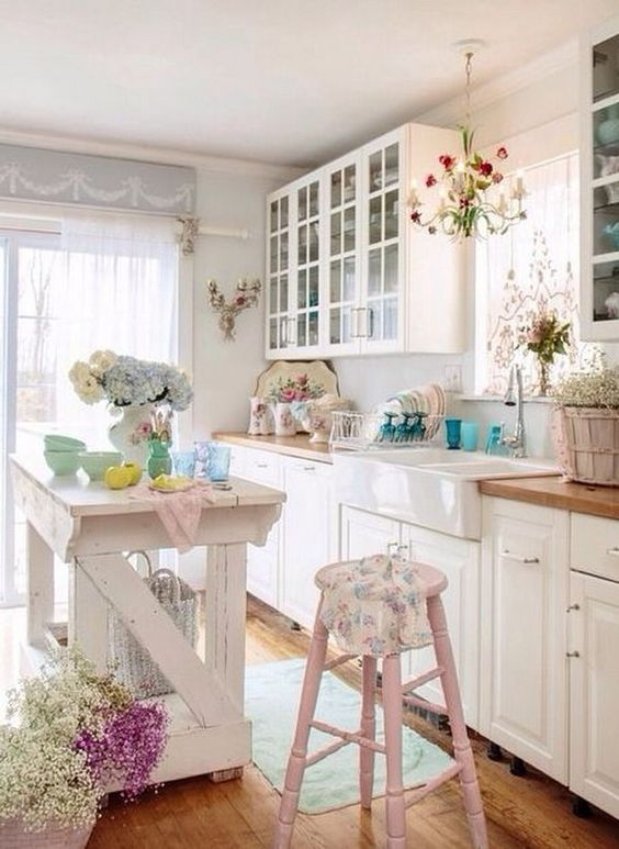 a lovely shabby chic kitchen with white cabinets, pastel pink touches, floral prints, a kitchen island and French doors
