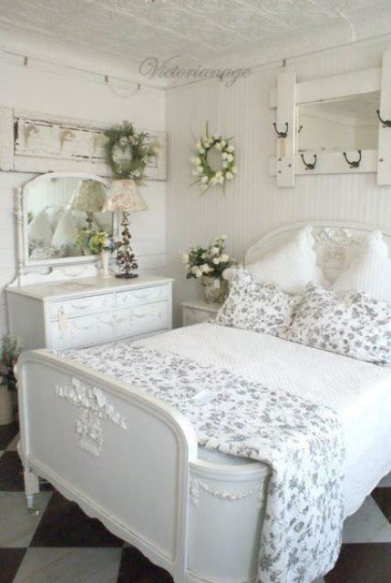 a lovely white shabby chic bedroom with refined furniture, floral bedding, a mirror on the wall, white blooms and a floral lamp