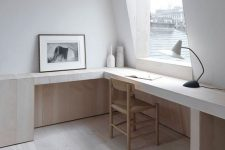 a minimalist and very neutral home office with a view, a built-in desk and a chair, a table lamp and an artwork