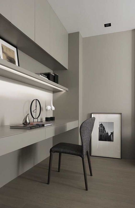 a minimalist grey home office with a sleek storage unit and a built-in shelf and desk with storage, a grey chair and some lovely artworks