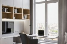 a minimalist home office nook with sleek grey storage units and built-in lights, a built-in desk and a black chair plus a view of the city