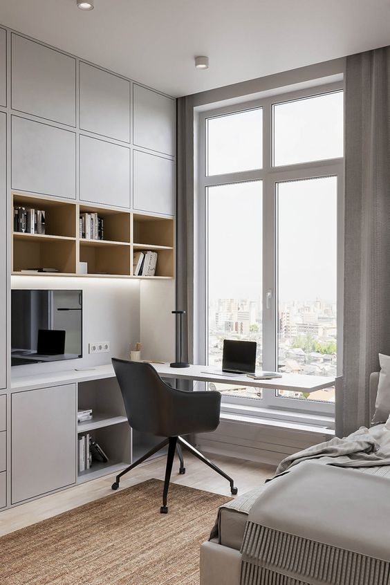 a minimalist home office nook with sleek grey storage units and built in lights, a built in desk and a black chair plus a view of the city