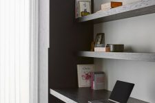 a minimalist home office with a sleek storage unit, open shelves, a built-in desk and a black chair plus greenery in a vase