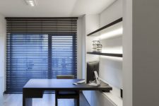 a minimalist home office with an open shelving unit with lights, a built-in desk and a blakc chair plus a floor to ceiling window