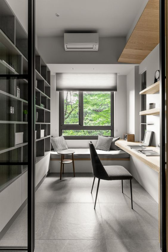 a minimalist home office with a built in storage unit, a built in desk and shelves, a windowsill daybed and pillows