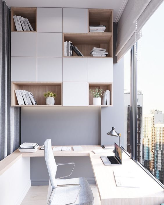 a minimalist home office with a gorgeous view, a shelving unit, a large corner desk and a table lamp is a chic and inspiring space