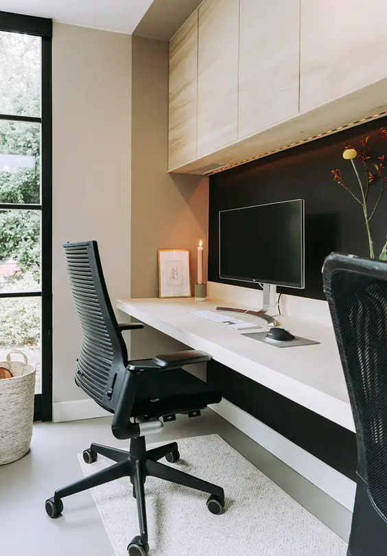a minimalist home office with a light-stained storage cabinet, a floating desk, a black chair and a black accent wall is a welcoming space