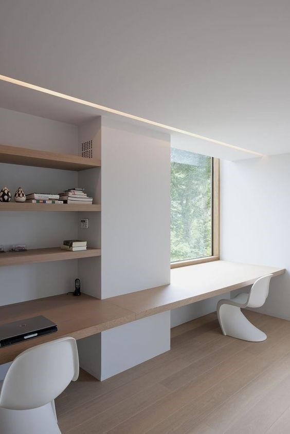 a minimalist home office with built-in shelves, a floating desk and sculptural chairs plus a window with a view
