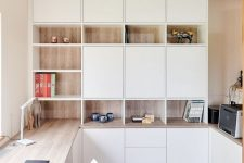 a minimalist home office with white and stained storage units, with a built-in desk and some pretty decor is very chic