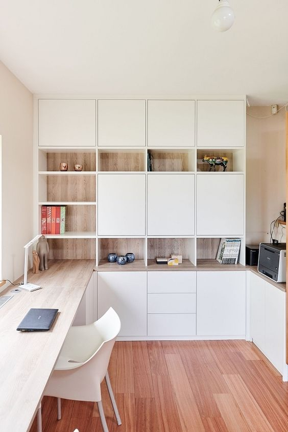 a minimalist home office with white and stained storage units, with a built in desk and some pretty decor is very chic