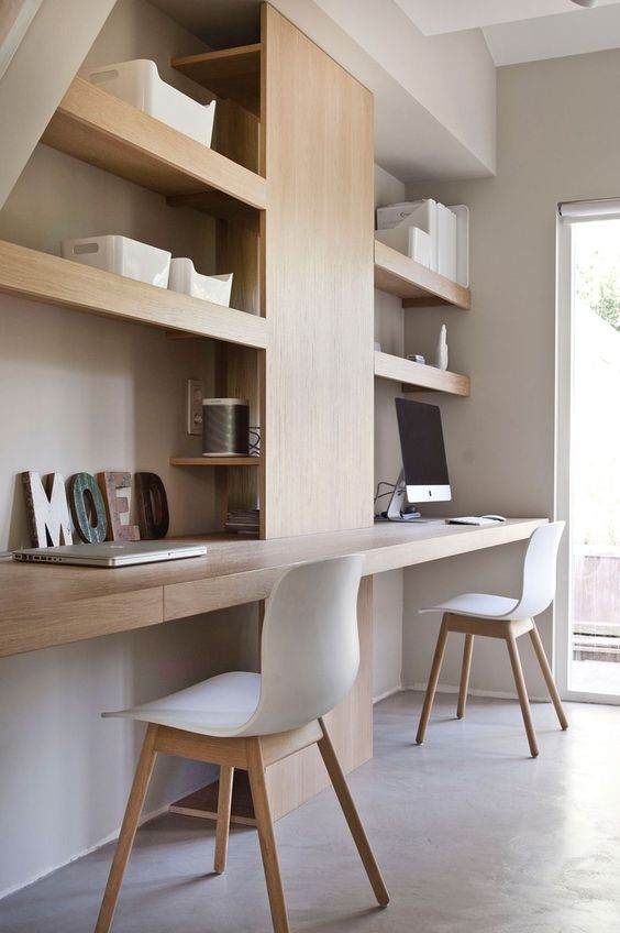 a minimalist shared home office with built-in shelves and desks, white chairs and a window for more natural light and a view
