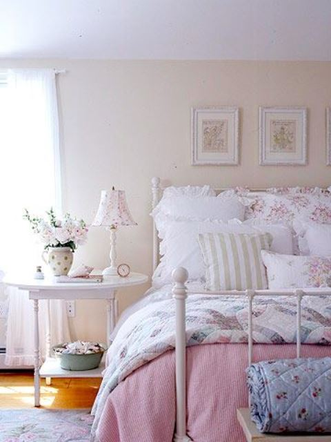 a neutral and pastel bedroom in shabby chic style, with a white forged bed, white wooden furniture, floral bedding and a gallery wall