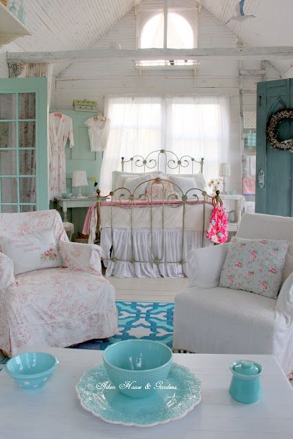 a neutral and pastel shabby chic bedroom with a forged bed, a minty door, floral bedding and white furniture
