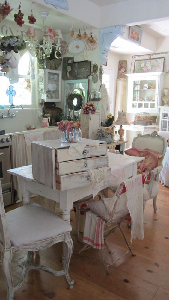 a neutral and pastel shabby chic kitchen and dining space with curtains on the cabinet, lots of floral prints, refined furniture and hanging lamps