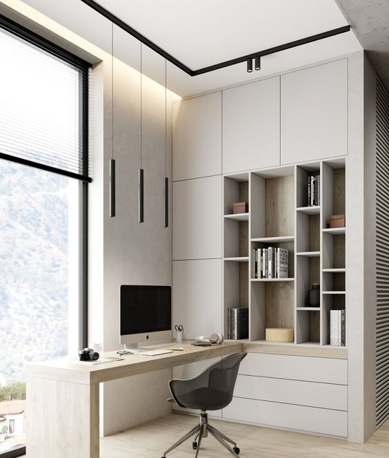 a neutral minimalist home office with light grey storage units and open storage compartments, a built-in desk and a black chair is chic