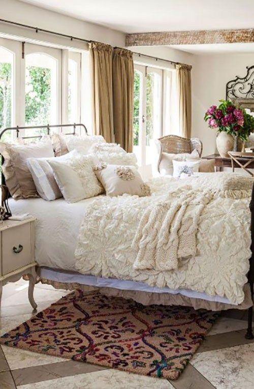 a neutral shabby chic bedroom with a metal bed, refined neutral furniture, ruffle and lace bedding and potted blooms