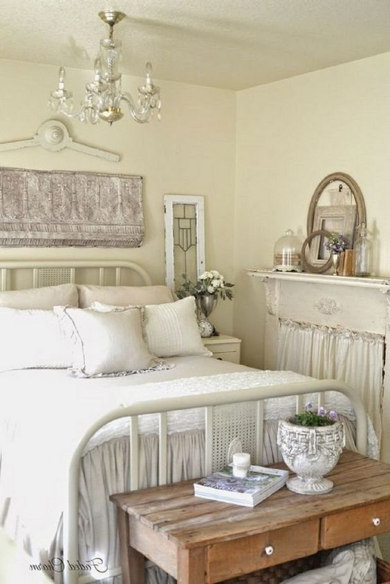 a neutral shabby chic bedroom with buttermilk walls, a metal bed, wooden furniture and a non-working fireplace and a crystal chandelier
