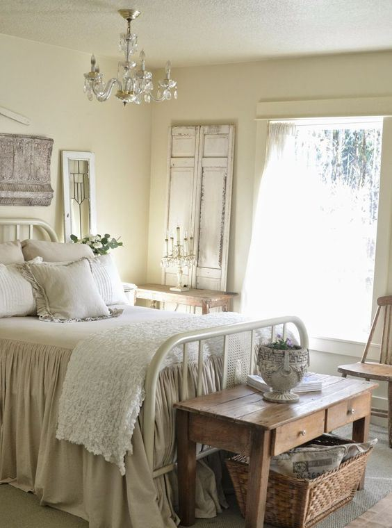 a neutral shabby chic bedroom with buttermilk walls, a white forged bed, wooden furniture, a crystal chandelier and ruffle bedding