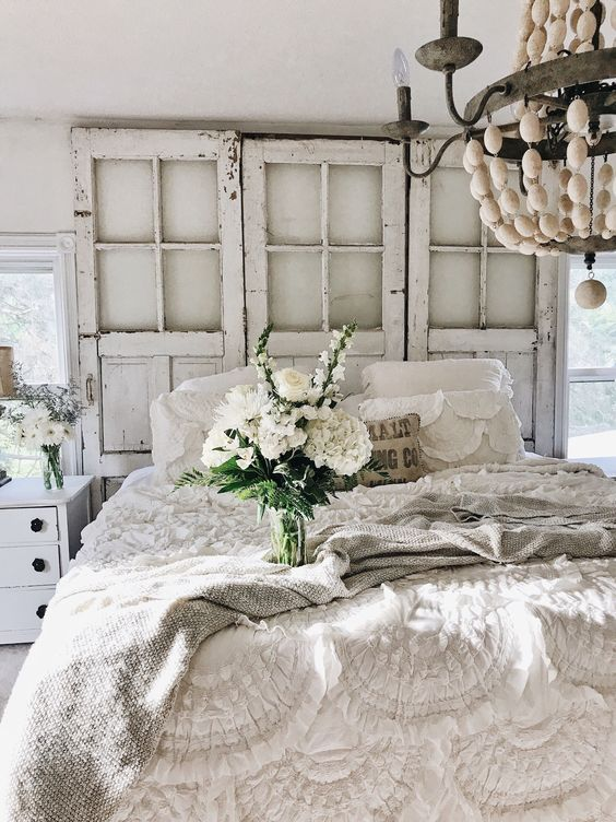a neutral shabby chic bedroom with vintage doors instead of a headboard, ruffle and lace bedding, a bead chandelier and blooms