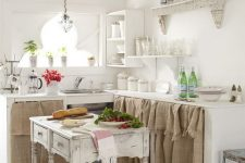 a neutral shabby chic kitchen with cabinets with burlap hanging, a shabby kitchen island, refined shelves and potted greenery