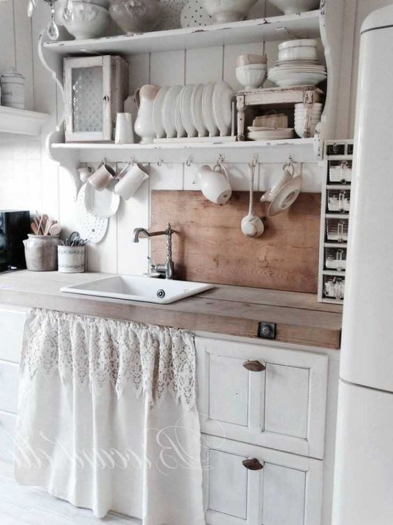 a neutral shabby chic kitchen with vintage cabinets, open shelving, stained countertops and a backsplash, a lace curtain for covering