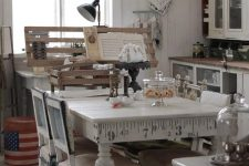 a neutral shabby chic kitchen with white cabinets and glass ones, a vintage table and chairs, metal retro lamps and aqua-colored clocks