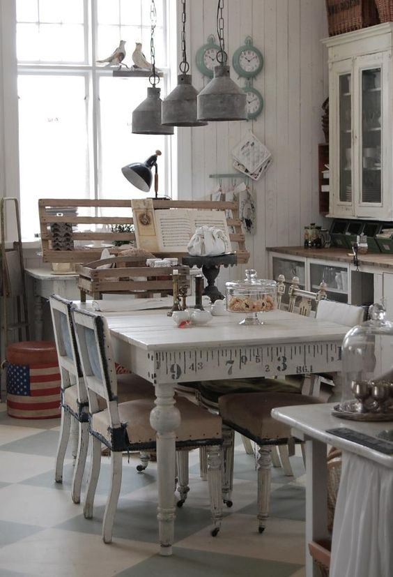 a neutral shabby chic kitchen with white cabinets and glass ones, a vintage table and chairs, metal retro lamps and aqua colored clocks