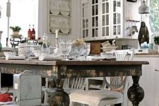 a neutral shabby chic kitchen with white walls and cabinets, a black shabby table, a crystal chandelier, vintage glasses and plates