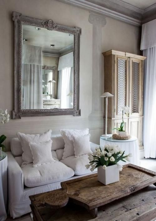 a neutral shabby chic living room with a white sofa, a large mirror, a rough wooden table and a large vintage cabinet